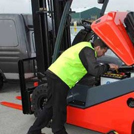 picture of man fixing forklift
